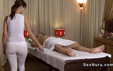 Busty masseuse in undershirt gives massage