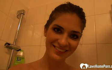 Horny chick plays with her pussy dimension showering